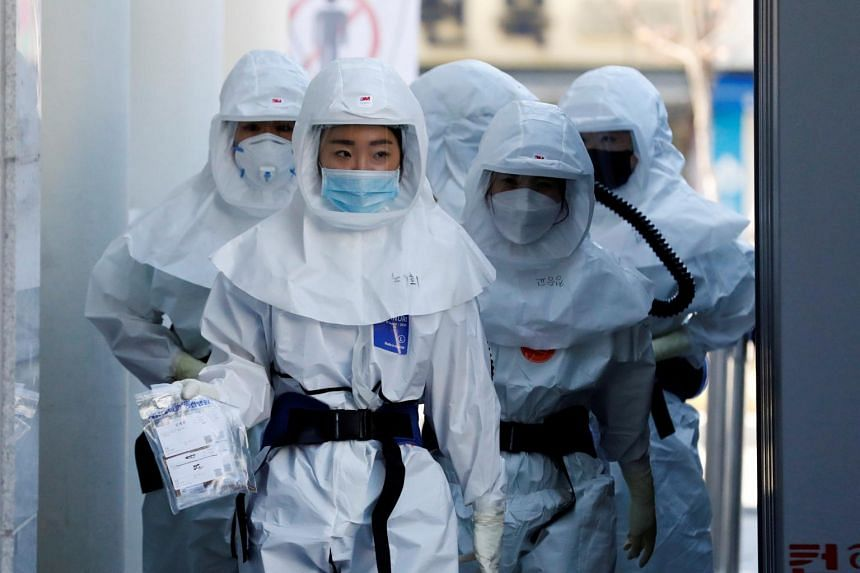 Medical workers head to a hospital facility to treat coronavirus patients in Daegu, South Korea, on March 14, 2020.