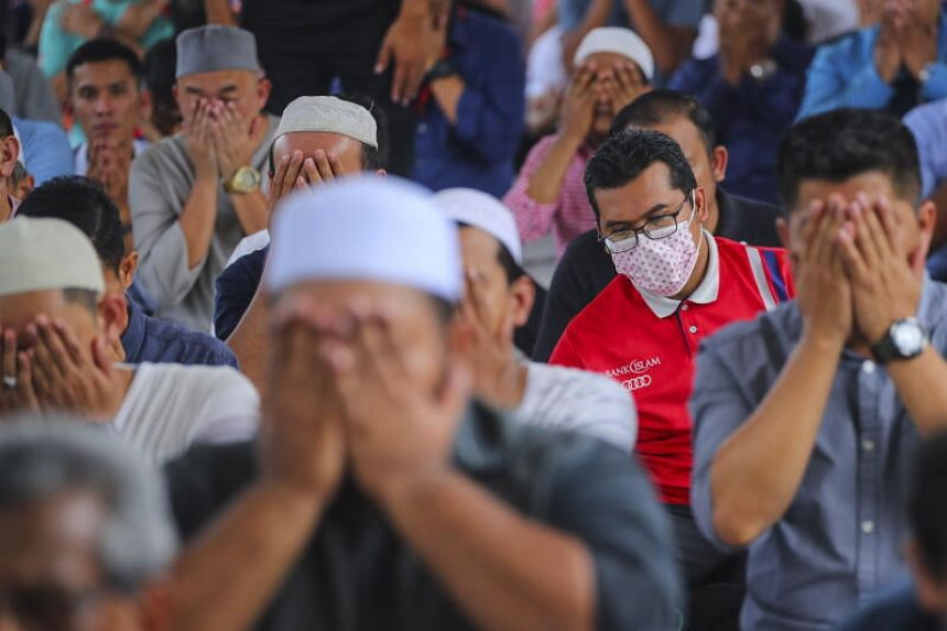 A man wears a mask during Friday prayers at the National Mosque in Kuala Lumpur, Malaysia, on March 13, 2020.
