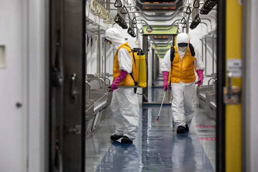Workers wearing protective suits and masks spray disinfectant inside a Seoul Metro subway train during disinfection operations in Seoul, South Korea, on March 11, 2020.