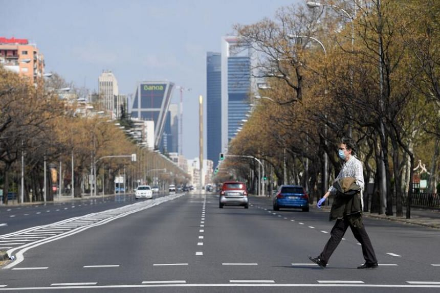 A man wearing a face mask crosses the usually busy La Castellana avenue in Madrid on March 15, 2020.