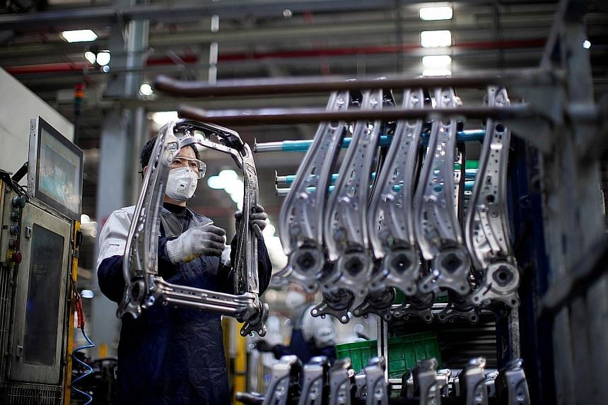 A masked employee at a car factory in Shanghai in February - before the Chinese authorities virtually shut down the world's second-largest economy to stop the coronavirus outbreak. Now, factories are re-opening but face new problems. Tens of millions
