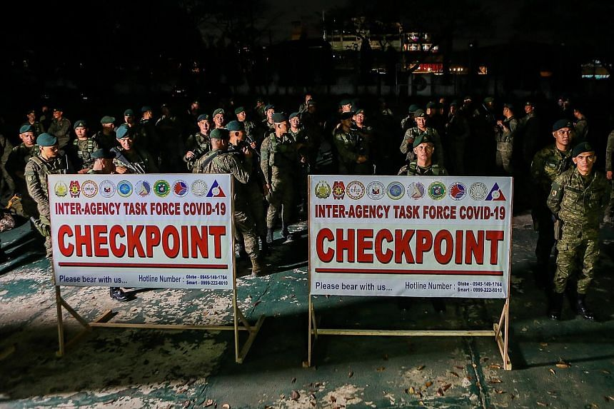 Philippine soldiers awaiting deployment at checkpoints yesterday in Valenzuela, south of Manila, as Metro Manila began a month-long lockdown amid a growing number of local Covid-19 cases.