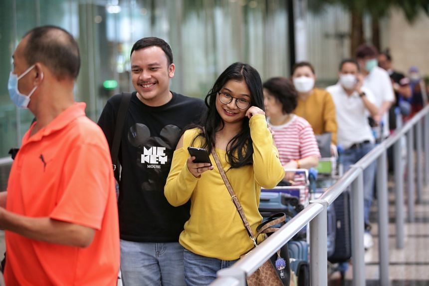 Indonesian freelancer Nadine (right), with her husband, Rama, who is based in Singapore to train as a pilot with Garuda, after she arrived at Changi Airport Terminal 3 on March 16, 2020.