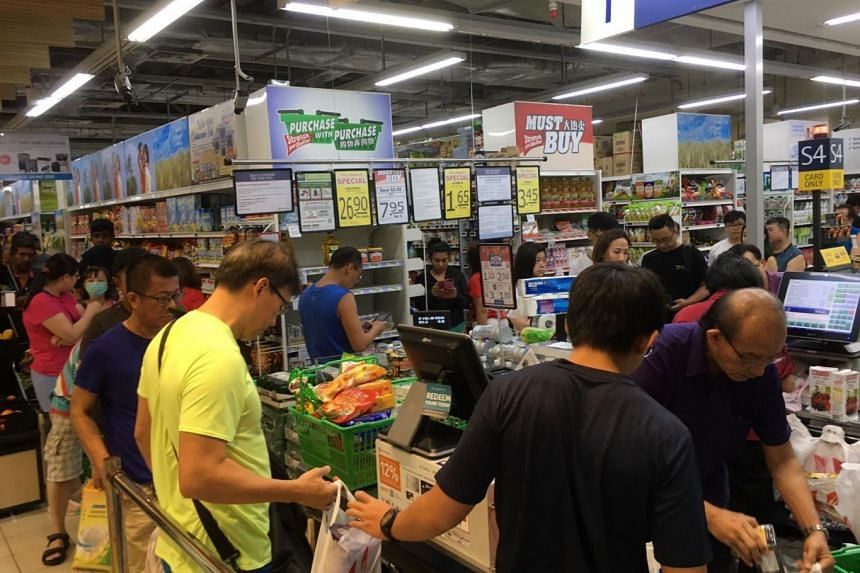 Shoppers queueing up to buy food products at Bukit Panjang NTUC on March 16, 2020. Many flocked to supermarkets following Malaysia's announcement of new measures to restrict movement nationwide.
