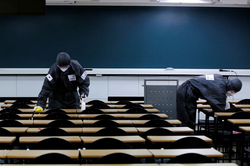 """Soldiers cleaning desks with disinfectant in the classroom of a cram school for civil service examinations in Daegu, South Korea. The city has been declared a """"special disaster zone"""", which means the government can subsidise up to 50 per cent of rest"""