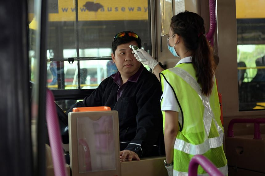 Temperature checks on a bus at Woodlands Checkpoint. The exemption from restrictions on Asean states means workers who commute daily between Singapore and Malaysia can still do so.
