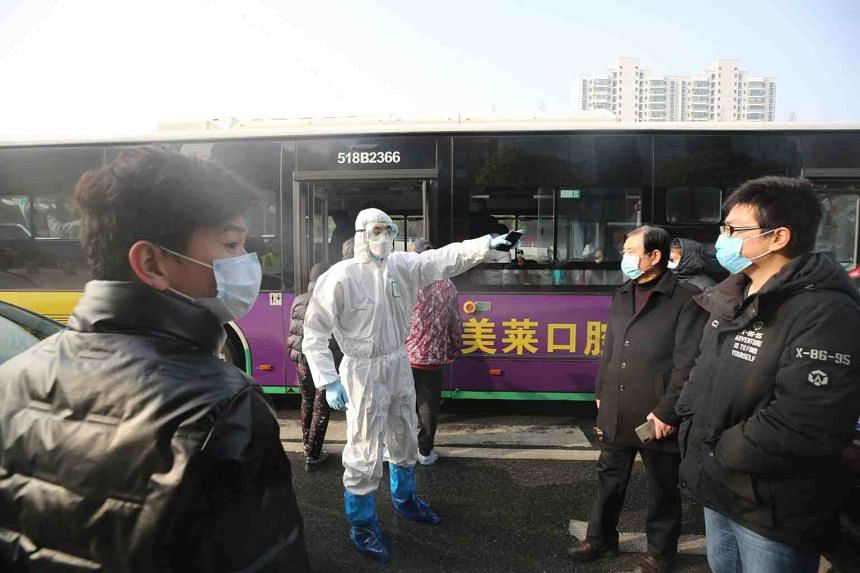 A medical worker gives instructions to people at a hospital in Wuhan on March 14, 2020.