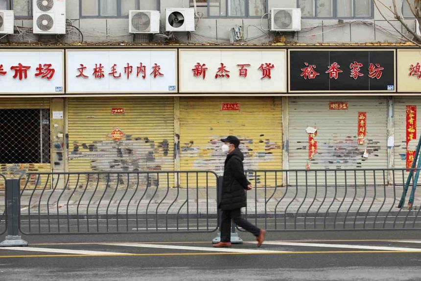 A man wearing a face mask walks past closed shops in Wuhan on Feb 7, 2020.