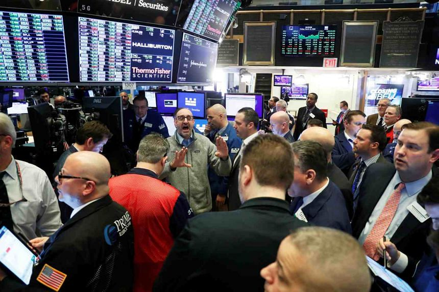 Traders work on the floor of the New York Stock Exchange shortly after the closing bell, on March 13, 2020.