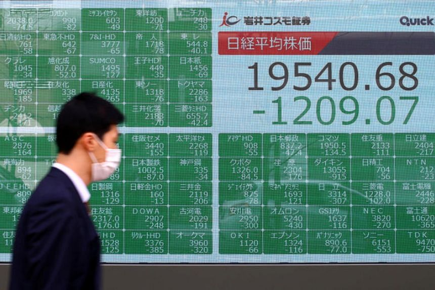 A passerby wearing a protective face mask walks past an electronic display showing Asian markets indices outside a brokerage in Tokyo, Japan, on March 9, 2020.