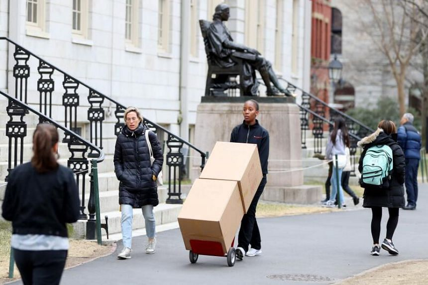A student moving her belongings through Harvard Yard on the campus of Harvard University on March 12, 2020 in Cambridge, Massachusetts.