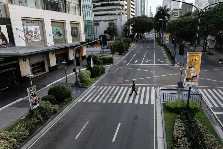 A man walks on an empty road in Makati City, in the Metro Manila region of the Philippines, on March 17, 2020.