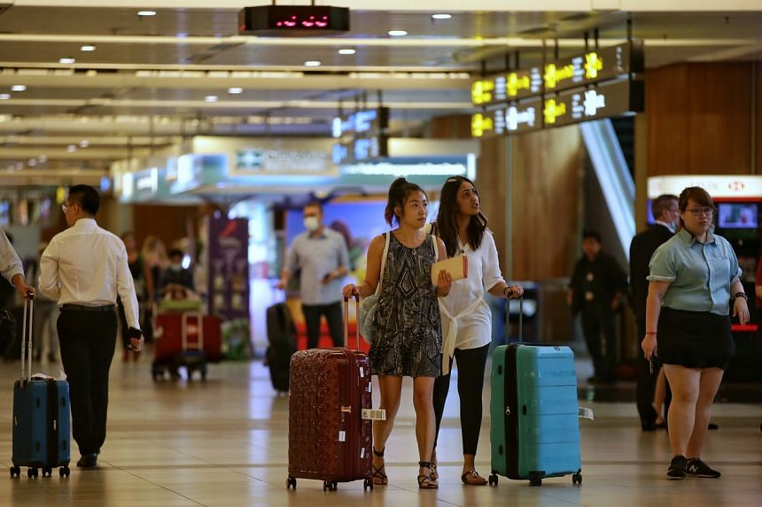 Travellers arrive at Changi Airport on March 16, 2020.