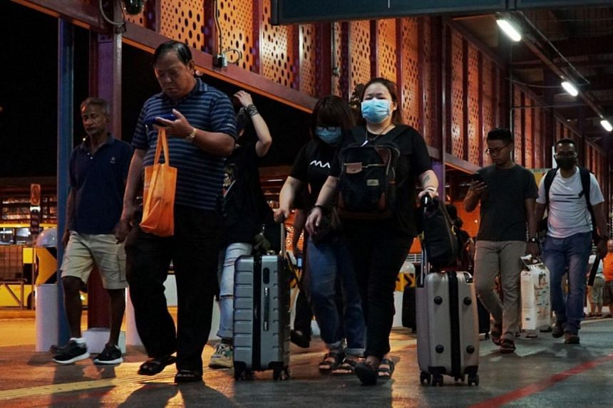 Travellers from Malaysia arrive at Woodlands interchange with their luggage on March 17, 2020.