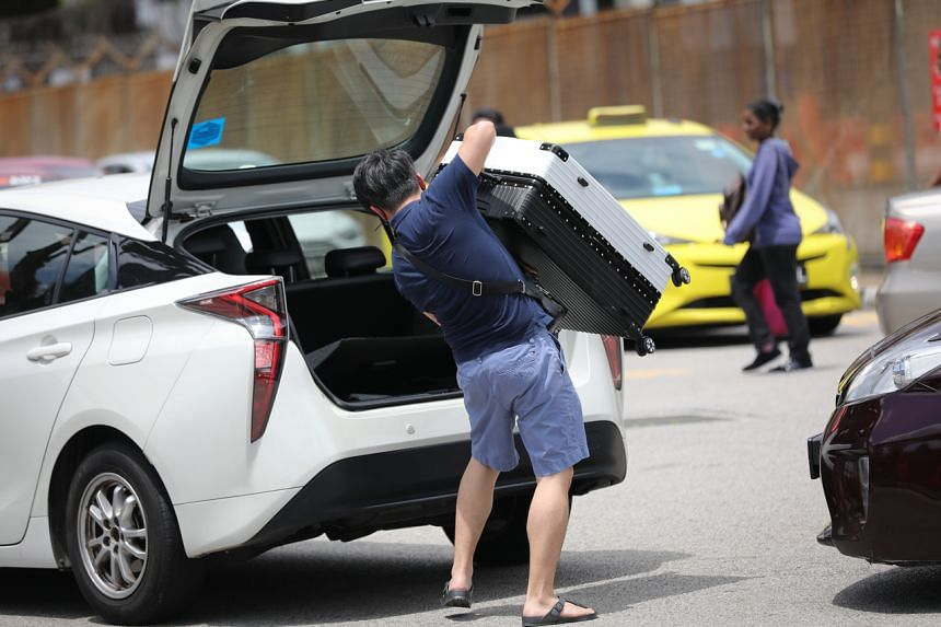 People arrive in Singapore from Malaysia with luggage near the Woodlands checkpoint on March 17, 2020.