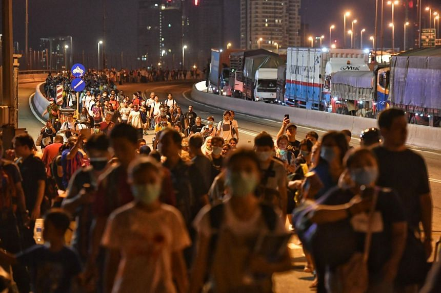 People walk across the Causeway after the Malaysian Checkpoint on March 17, 2020.