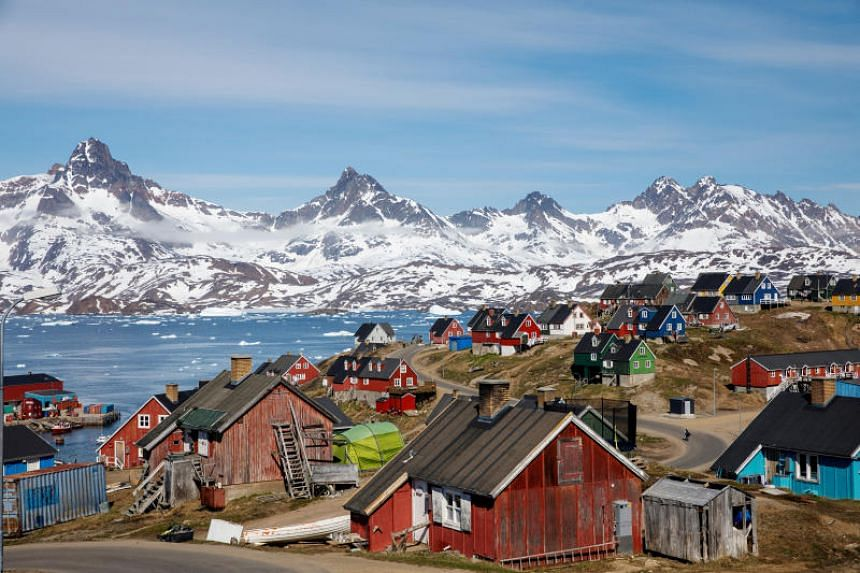 In a file photo taken on June 15, 2018, snow-covered mountains rise above the harbour and town of Tasiilaq, in Greenland.