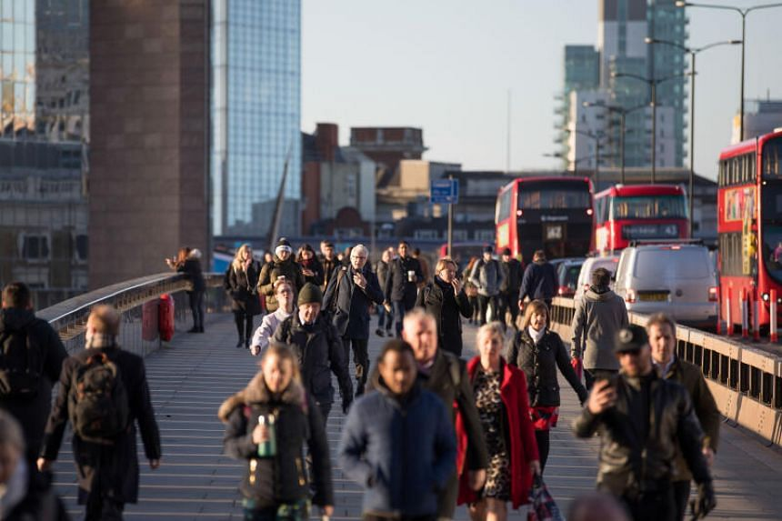 Commuters walk across London Bridge during morning rush hour in London, Britain, on March 16, 2020.