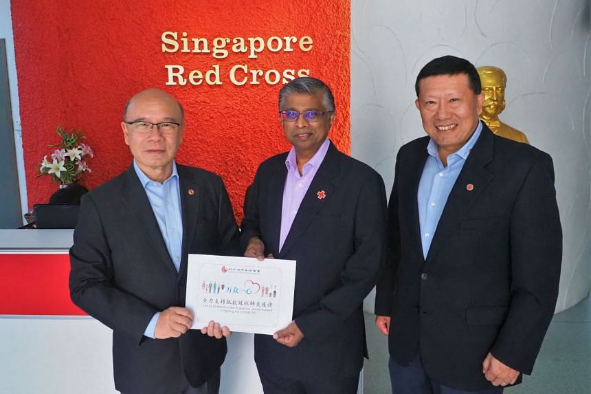 A cheque of $145,501 collected from the second phase of SCCCI's donation appeal was presented by Mr Charles Ho Nai Chuen, vice-president of SCCCI (left) to Mr Benjamin William, secretary general and chief executive of Singapore Red Cross Society (c