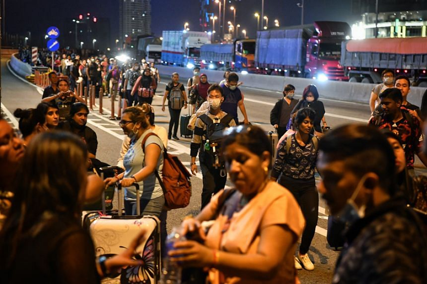 Commuters walk across the Causeway after the Malaysian checkpoint on March 17, 2020.