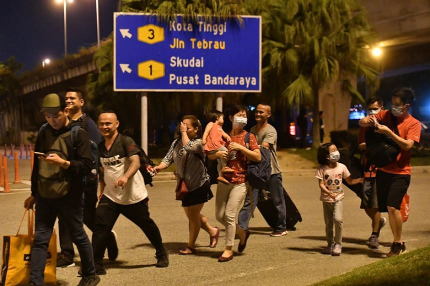 Commuters walking towards the Malaysian checkpoint in Johor Baru on March 17, 2020.