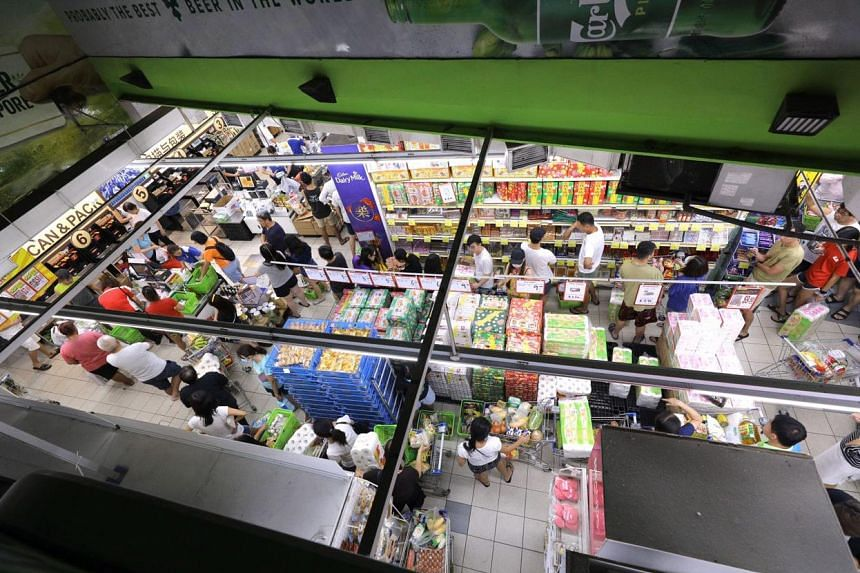 Shoppers at a Sheng Siong supermarket in Serangoon North Ave 5 after midnight on March 17, 2020.