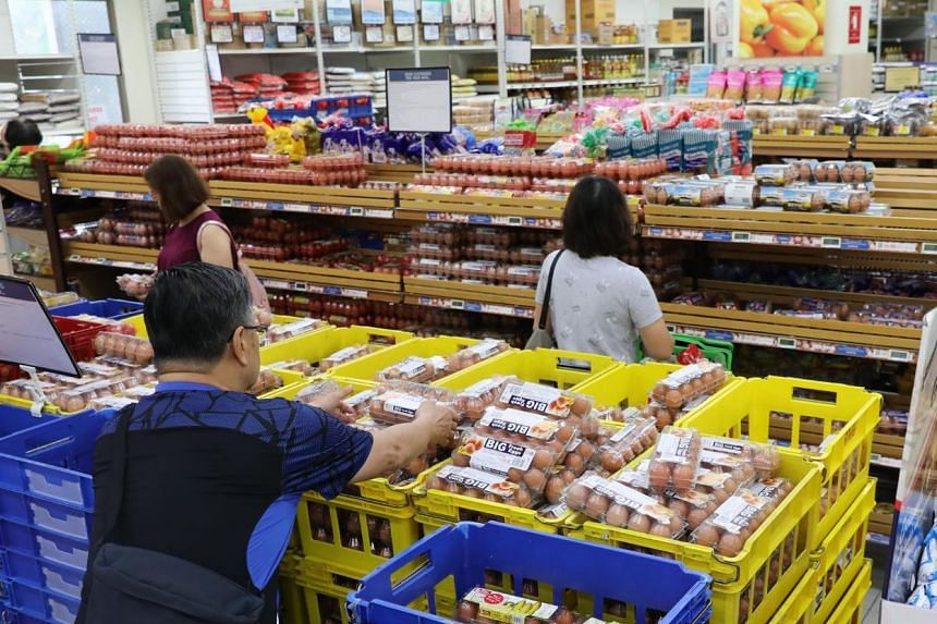 People buy eggs and other groceries at the Hougang 1 outlet of FairPrice Xtra on March 17, 2020.