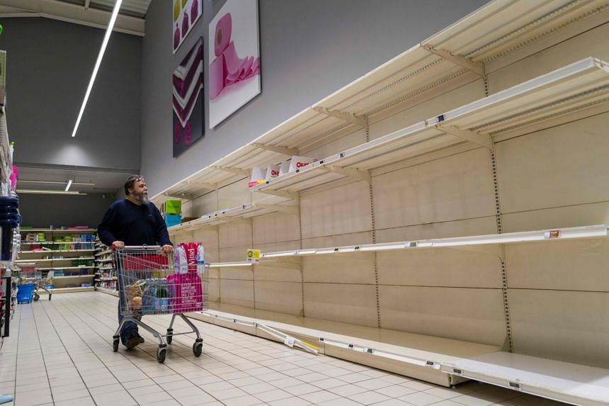 A man looks at empty shelves at the toilet paper section of a supermarket in France on March 16, 2020.