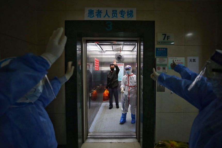 Medical staff wave goodbye to a recovered coronavirus patient at the Red Cross Hospital in Wuhan on March 16, 2020.