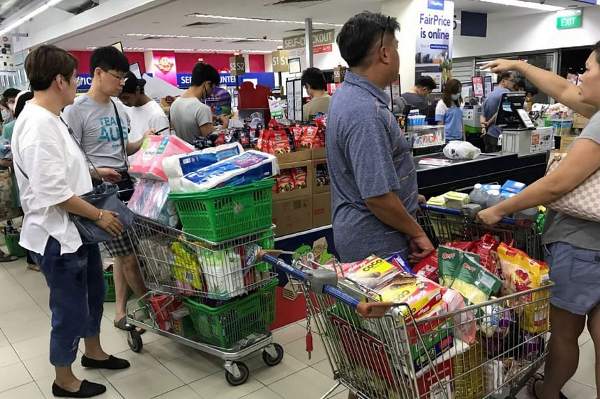Shoppers with packed trolleys at the FairPrice outlet in Clementi Central at 12.15am today. The country is not facing any shortages, and Trade and Industry Minister Chan Chun Sing urged Singaporeans to continue to purchase in a responsible manner and