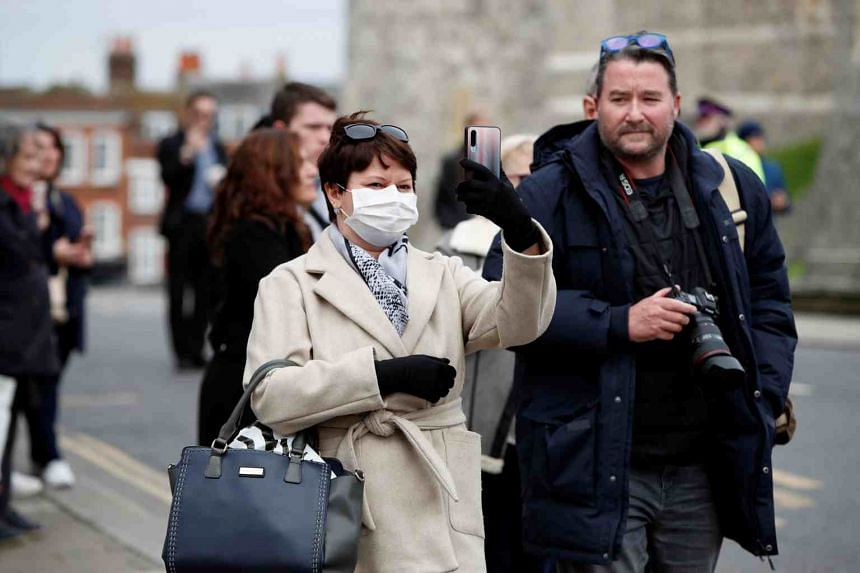 A woman wearing a face mask takes a photograph in Windsor, Britain, on March 17, 2020.