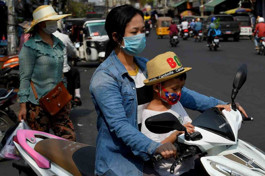 A woman and her son wear face masks as they ride a motorcycle along a street in Phnom Penh, Cambodia, on March 17, 2020.