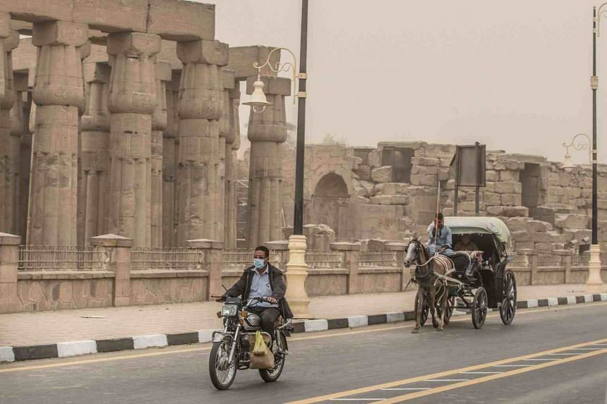 A mask-clad Egyptian rides his motorcycle amid a sandstorm near the Luxor Temple in Luxor, Egypt, on March 12, 2020.