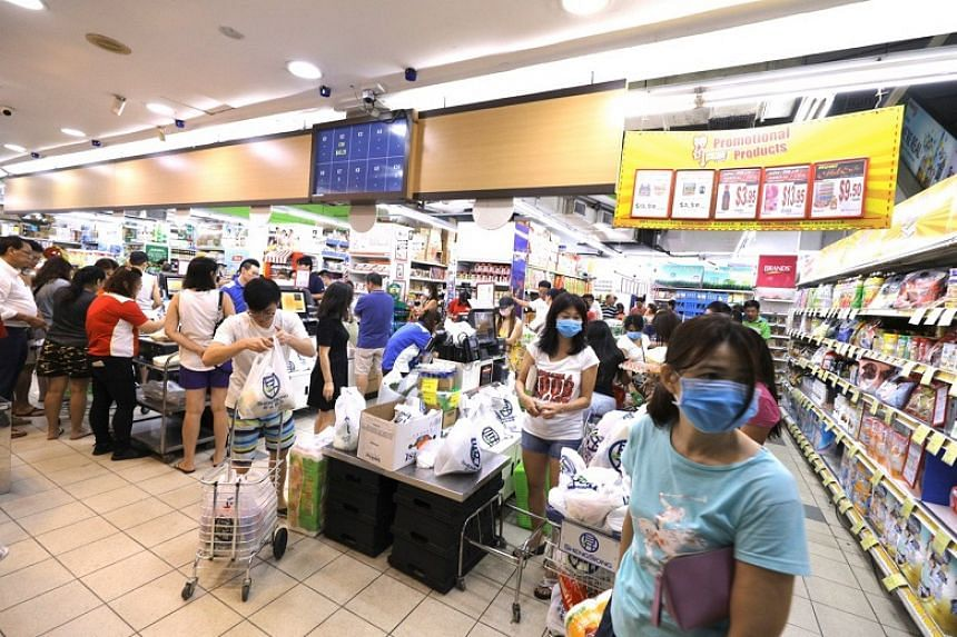 Shoppers at a supermarket in Serangoon North after midnight on March 17, 2020.