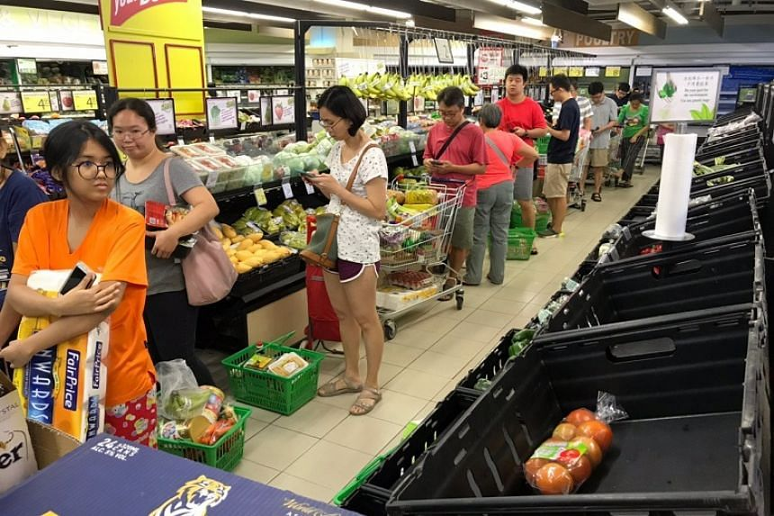 Shoppers queue up at a supermarket in Clementi after midnight on March 17, 2020.