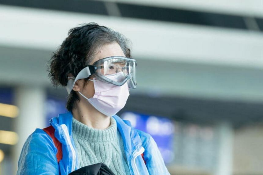 A traveller wearing a mask and goggles is seen at Frankfurt Airport, Germany, on March 16, 2020.