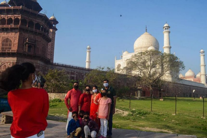 Visitors wearing face masks have their picture taken outside Taj Mahal following its closure in Agra on March 17, 2020.