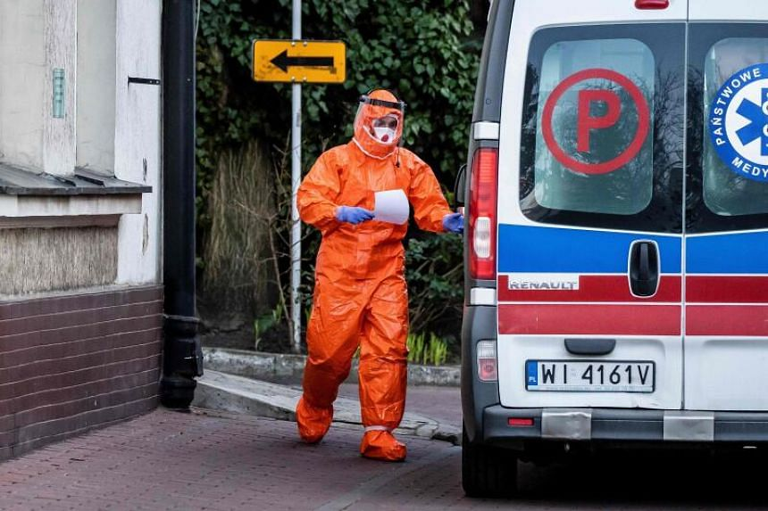 A paramedic, wearing a protective outfit, walks towards his vehicle at an infectious hospital in Warsaw, Poland, on March 14, 2020.