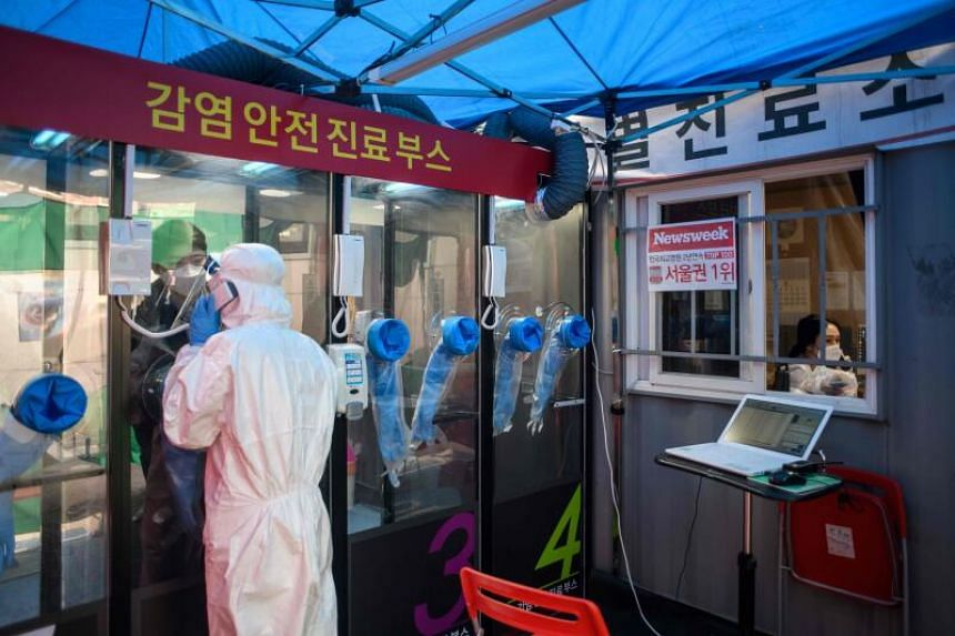 A man speaks to a nurse at a testing booth outside Yangji hospital in Seoul, South Korea, on March 17, 2020.