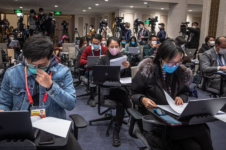 Journalists wearing protective face masks wait for a press conference by Mao Shengyong, a spokesman for China's National Bureau of Statistics, in Beijing, China, March 16, 2020.
