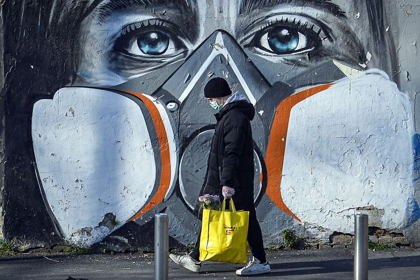 A man walks with his groceries beside a mural portraying a person wearing a gas mask, in Milan, Italy.