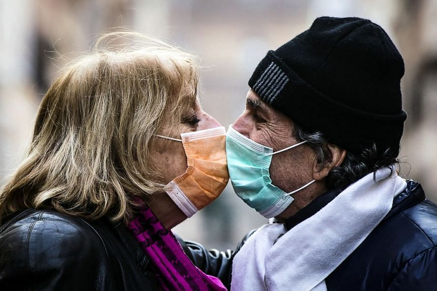 A couple wearing protective face masks kiss in the Borgo Pio district of Rome, Italy, March 17, 2020.