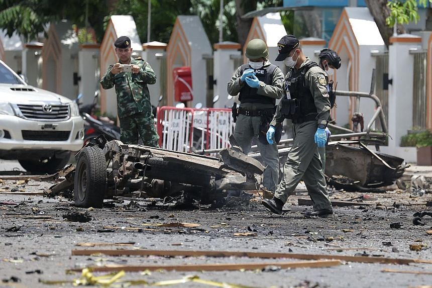 Police investigators inspecting the wreckage of a car bomb following explosions in Thailand's restive south yesterday.