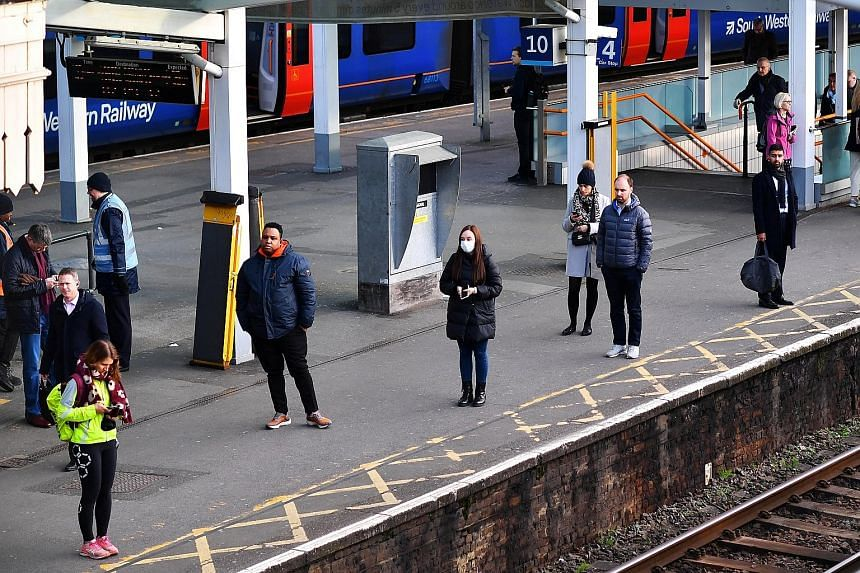 Commuters standing apart as they waited for trains at Clapham Junction during rush hour in London yesterday. Britain's new measures include household isolation if a family member has Covid-19 symptoms, staying away from pubs, clubs, restaurants and t