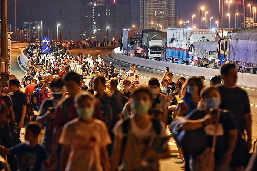 People walking across the Causeway from Malaysia towards Woodlands Checkpoint shortly before 10pm yesterday. Malaysians are barred from travelling abroad from today till March 31. Singapore companies affected by the travel restrictions will get help