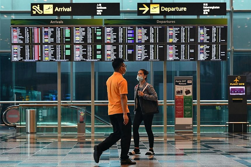 People wearing face masks at Changi Airport. National Development Minister Lawrence Wong pointed out yesterday that the majority of imported cases - which form the bulk of recent Covid-19 cases - are Singaporeans, permanent residents and long-term pa