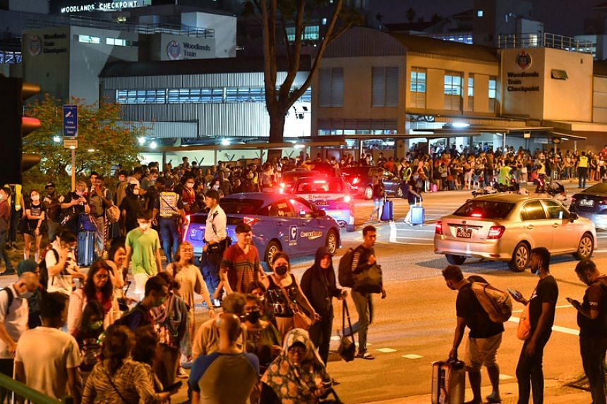 A crowd at a passenger pick-up point near the Woodlands Train Checkpoint at around 1.15am on March 18, 2020.