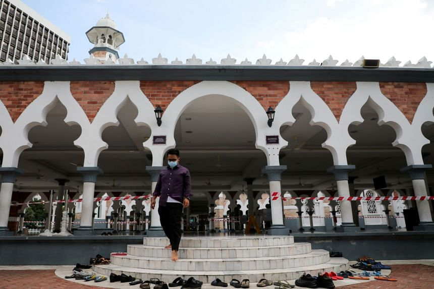 A man wearing a protective mask walks down the stairs of a mosque in Kuala Lumpur on March 16, 2020.