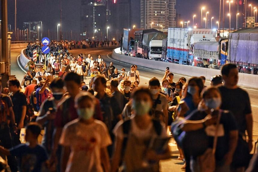 People walking across the Causeway from Malaysia towards Woodlands Checkpoint shortly before 10pm on March 17, 2020. Beginning March 18, the border between Malaysia and Singapore has been locked down.