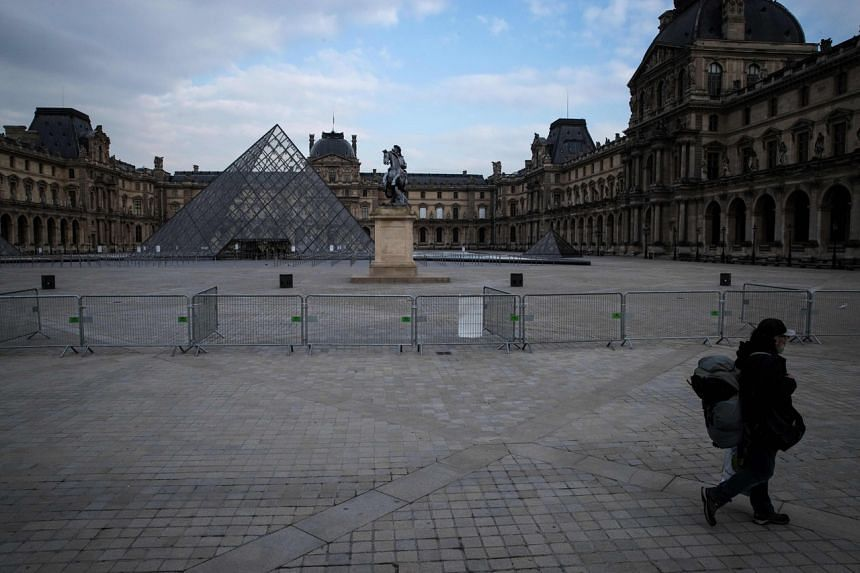 A man walks by the Louvre Museum in Paris on March 17, 2020, as a strict lockdown comes into in effect.